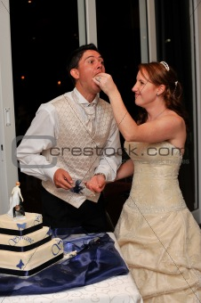 Bride feeding the groom wedding cake with her hand and smiling