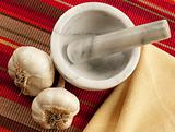 Garlic bulbs wth mortar and pestle on cloth