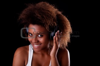 Beautiful black woman happy listening music in headphones, isolated on black background. Studio shot.