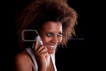 Beautiful black woman happy on the phone, isolated on black background. Studio shot.