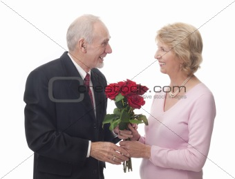 Elderly man giving red roses to elderly woman