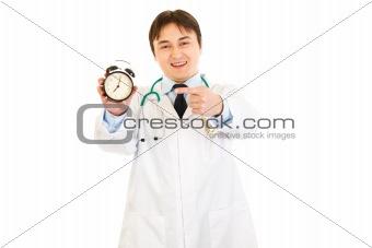 Smiling  medical doctor pointing finger on  alarm clock
