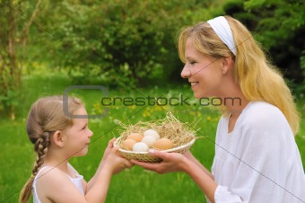 Mother and daughter holding fresh eggs