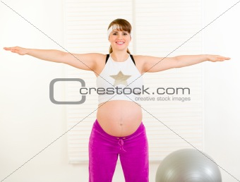 Smiling beautiful pregnant woman doing exercise at home