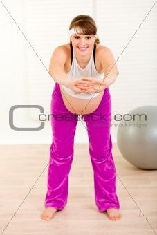Smiling beautiful pregnant woman making gymnastics  at home