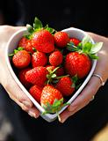 strawberries in heart shape bowl with hands