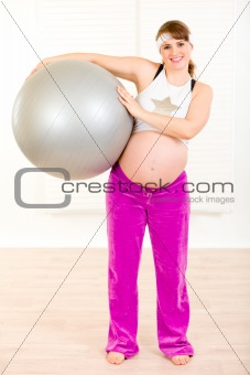 Smiling beautiful pregnant woman holding fitness ball in hands