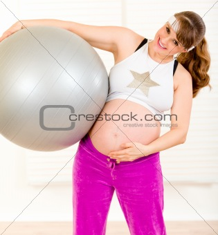 Smiling beautiful pregnant woman holding fitness ball and touching her belly