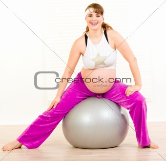 Smiling beautiful pregnant woman doing exercises on  fitness ball at home
