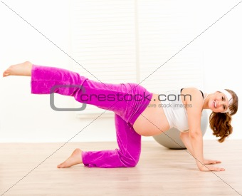 Smiling beautiful pregnant woman doing aerobics exercise  at home