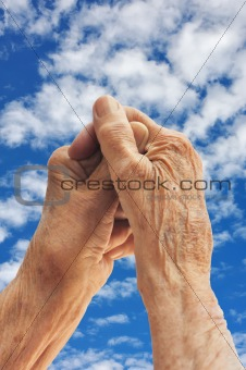 Hands of senior woman over sky