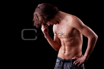 a tired and sweat  young man in topless, isolated on black. Studio shot.