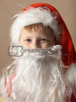 Little boy in Santa Claus suit with beard