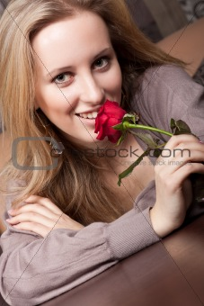 Attractive young girl with a red rose