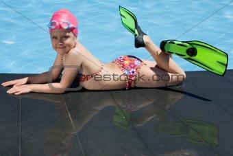 Little child in bathing cap, glasses, fins near swimming pool