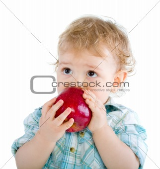 Beautiful baby boy eats red apple.