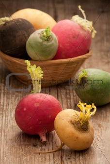 Group ripe variegated radishes in woven bowl on board