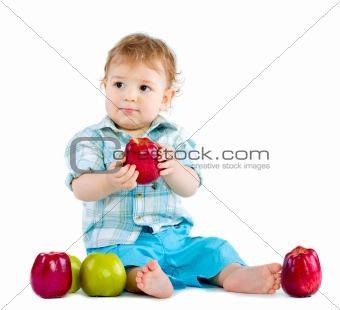 Beautiful baby boy eats red apple.