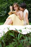 Teen girls reading a book outdoors