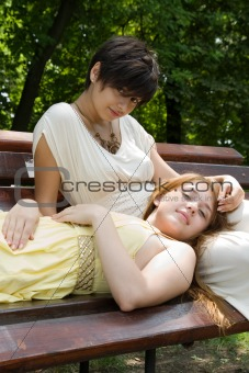Young girls on the bench in the park