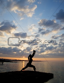 Silhouette of fit young woman doing stretching exercises on beac