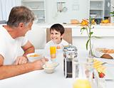 Father having his breakfast with his son