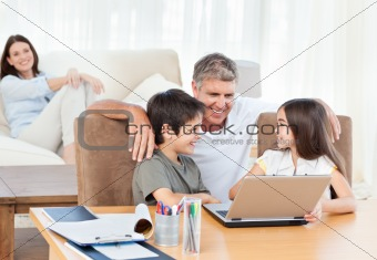 Children playing video games on the laptop while parents are looking about them