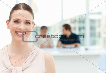 Businessman looking at the camera while his team is working in the background