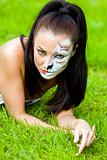 woman with face art on grass