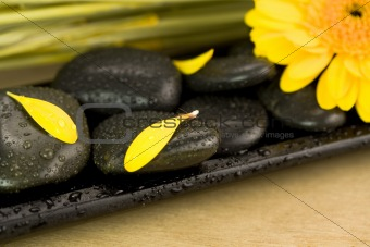 Spa setting with pebbles and yellow flower
