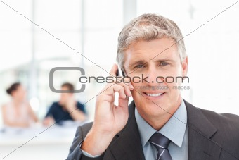 Businessman phoning while his team is working