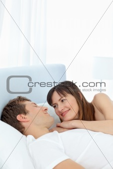 Happy couple lying down together on their bed
