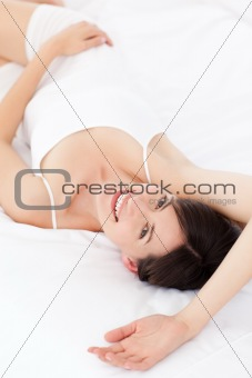 Pretty woman lying down on her bed