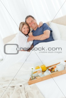 Lovely couple having breakfast in their bed