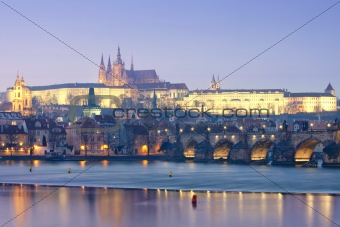 prague in winter - charles bridge and hradcany castle at dusk