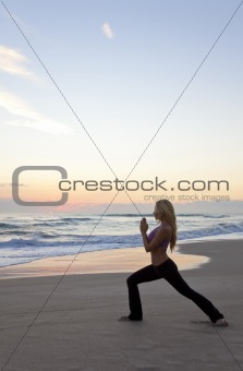 Beautiful Woman Practicing Yoga on Beach At Sunrise or Sunset