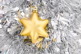 golden star, christmas decoration on silver tinsel