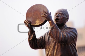 Statue of a man singing with drum