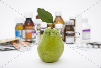 green pear in front of pills