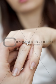 situation of inserting engagement ring into a finger