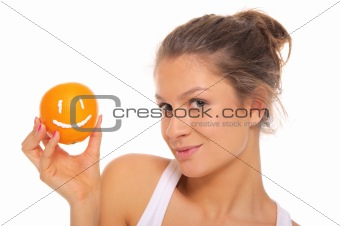 Woman holds orange with smile