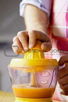 man preparing orange juice at home