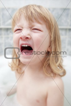 boy with long blond hair sitting in bathtub, screaming