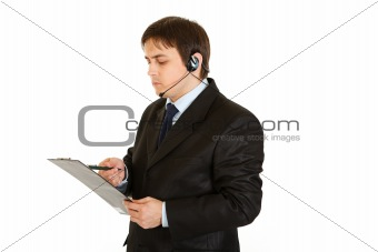 Serious businessman with headset checking notes in document