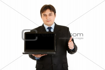 Smiling  businessman holding laptops blank screen and showing  thumbs up gesture