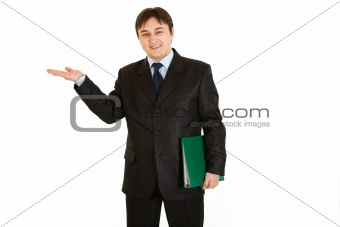 Smiling  businessman with folder presenting something on empty hand