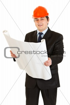 Smiling businessman in helmet holding building plan in hand