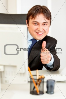 Smiling  businessman looking from monitor and showing thumbs up gesture