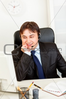 Smiling  businessman with  headset sitting at office desk and looking at computer monitor