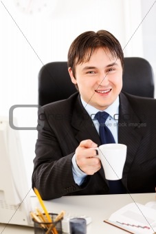 Smiling businessman  sitting at office desk  and holding cup of tea in hand